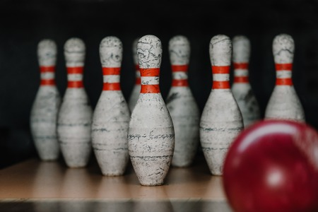 close-up shot of grungy bowling pins with red ball on foreground