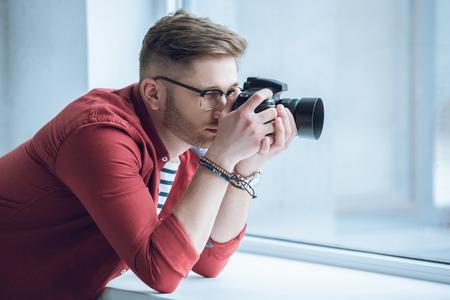 Joven fotógrafo disparando con cámara digital por ventana de luz