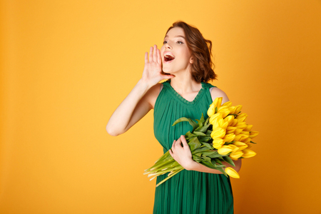 portrait of young woman with bouquet of yellow tulips shouting isolated on orange Archivio Fotografico