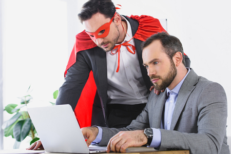 super businessman in mask and cape helping businessman with work in office Reklamní fotografie