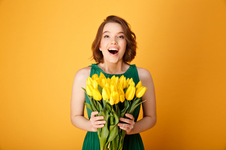 portrait of excited woman holding bouquet of yellow tulips isolated on orange