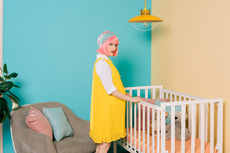 retro styled pregnant pin up woman with pink hair standing near wooden crib in child room