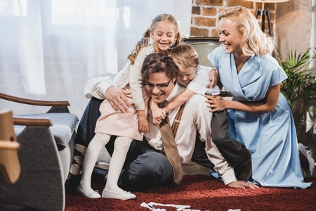 cheerful retro styled family hugging while playing dominoes at home Stock Photo