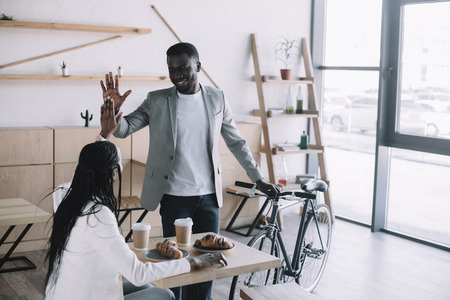 african american friends giving high five to each other at table in coffee shop
