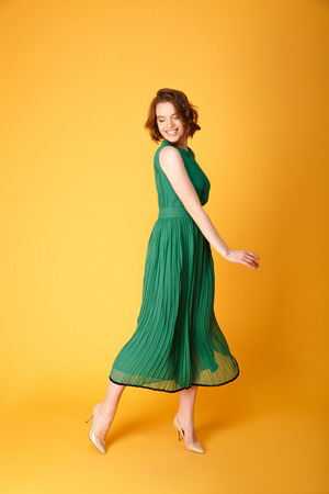 young cheerful woman in green dress isolated on orange Stock Photo