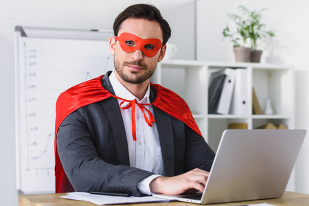 super businessman in mask and cape working with laptop in office and looking at camera