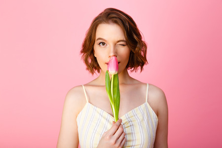 portrait of young woman in white dress with pink tulip flower winking at camera isolated on pink
