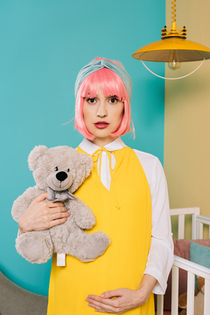 portrait of retro styled pregnant pin up woman with pink hair holding teddy bear in child room Stock Photo
