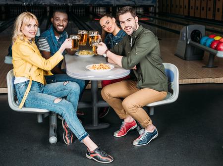 Gruppe von Freunden, die im Bowlingclub vor Gassen mit Bierkrügen klirren?