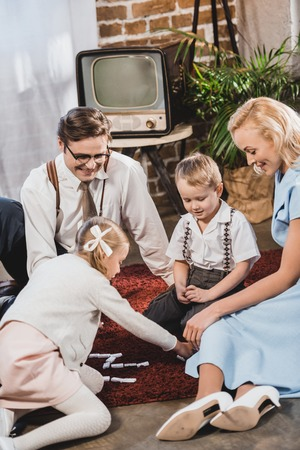 happy 50s style family playing dominoes together at home