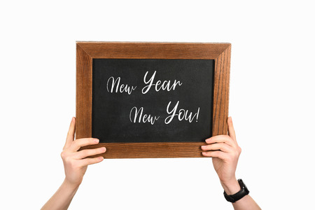 Cropped view of woman hands holding board with lettering new year new you isolated on white Stock Photo