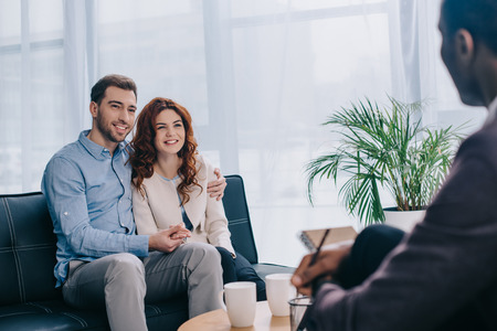 Smiling young couple sitting on sofa and talking to counselor with pencil in hand