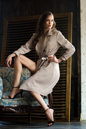 charming woman in elegant trench coat posing on armchair