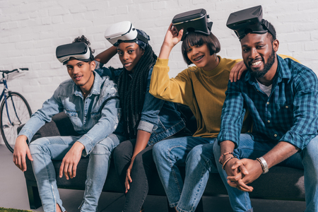 young multicultural friends with lifted up virtual reality headsets Imagens