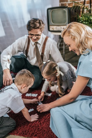 happy family with two kids playing dominoes together at home, 1950s style Stock Photo