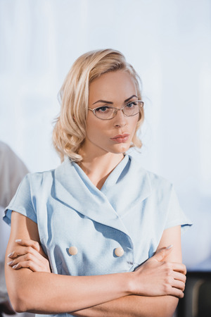 serious blonde woman in eyeglasses standing with crossed arms, 1950s style 写真素材