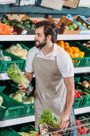 assistente di negozio sorridente che organizza le verdure fresche nel negozio di alimentari Archivio Fotografico