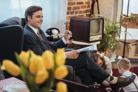 smiling man in suit reading newspaper in armchair while kids playing with domino tiles behind, 1950s style family