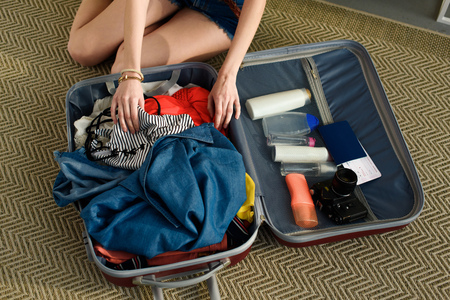 cropped view of girl packing suitcase with camera, passport and air ticket Stock Photo