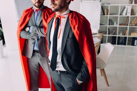 cropped image of super businessmen in capes in office Foto de archivo - 111233546