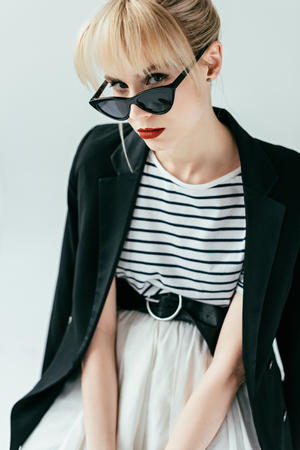 Fashionable blonde girl in sunglasses posing isolated on grey
