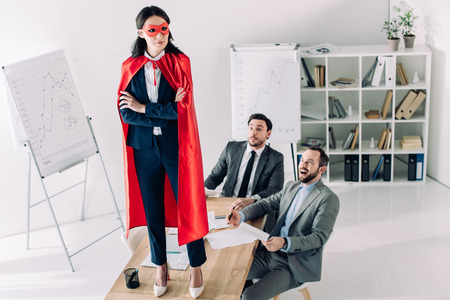 super businesswoman in mask and cape standing on table in office Foto de archivo - 111233573
