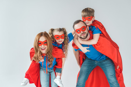 super parents piggybacking kids pretending to be superheroes isolated on grey