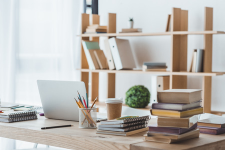laptop and educational books on table in light interior Stock Photo