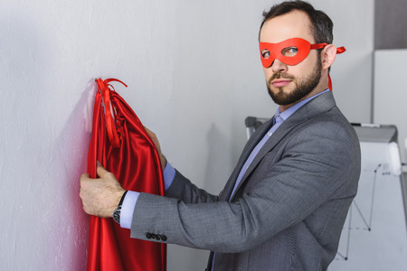 super businessman wearing mask and cape in office Stock Photo