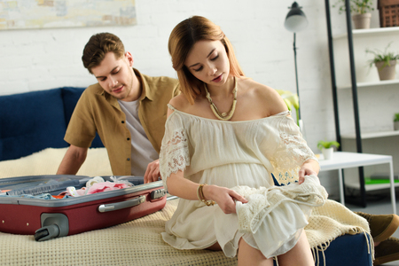 pregnant woman and husband preparing suitcase for hospital Standard-Bild - 111241183