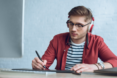 Freelancer man in headphones drawing with graphic tablet by table with computer