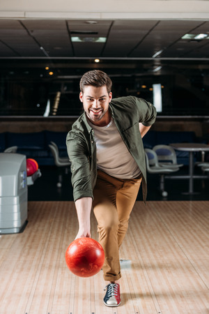happy young man throwing bowling ball at club