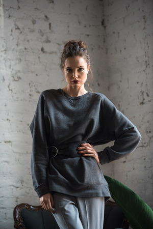 portrait of beautiful young woman in trendy jumper with belt standing with hand on waist and looking at camera