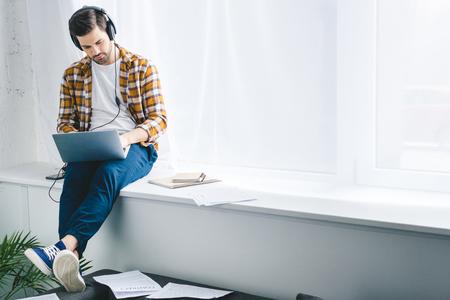 Man in headphones working on laptop and sitting on windowsill Stock Photo