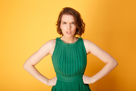 portrait of unsatisfied woman akimbo isolated on orange