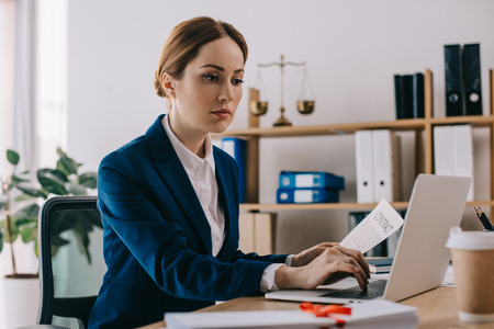 focused female lawyer working on laptop at workplace in office