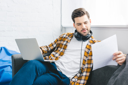 Businessman holing laptop and paper sitting on sofa at home office