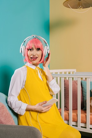 surprised pregnant pin up woman with pink hair listening music near baby cot in child room Stock Photo