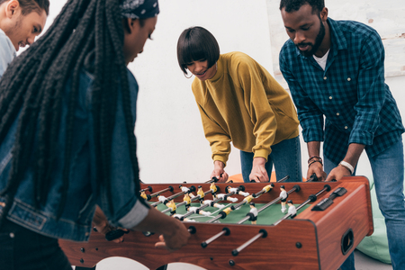 young multiethnic friends playing table soccer Stock Photo