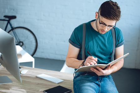 handsome young freelancer in eyeglasses taking notes at workplace