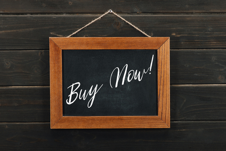 Board with lettering buy now hanging on wooden wall Stock Photo