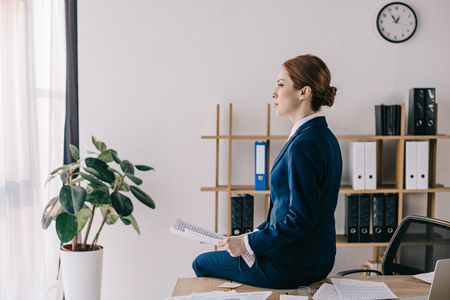 side view of pensive businesswoman with papers sitting on table in office