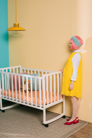 side view of retro styled pregnant pin up woman with pink hair standing near baby cot in child room Archivio Fotografico