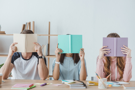 young students holding books in front of faces