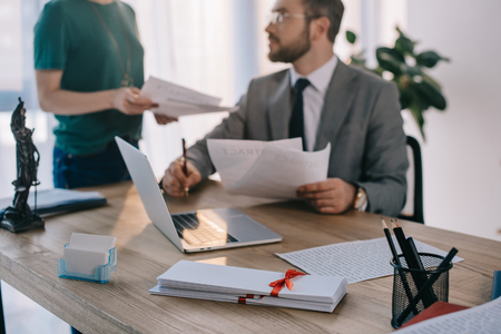 selective focus of lawyer and client with contract at workplace with laptop in office
