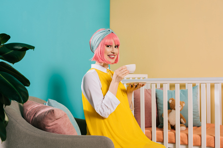 smiling pregnant pin up woman with pink hair sitting near baby cot with cup of tea Stock Photo