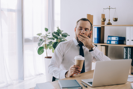 portrait of tired lawyer with coffee to go yawning at workplace in office