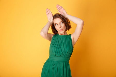 portrait of attractive woman showing bunny ears sign isolated on orange Stock Photo