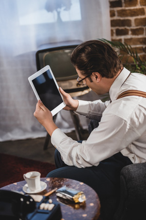 retro styled man in eyeglasses using digital tablet with blank screen