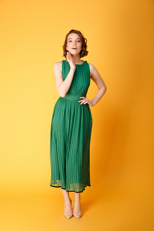 young pretty woman akimbo in green dress looking at camera isolated on orange